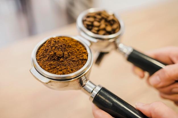 Alto angolo di due tazze di macchine da caffè tenute dal barista Foto Gratuite
