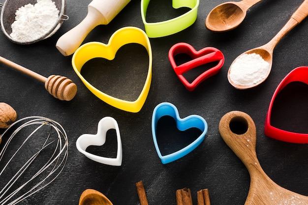 Alto angolo di forme colorate di cuore con utensili da cucina Foto Gratuite