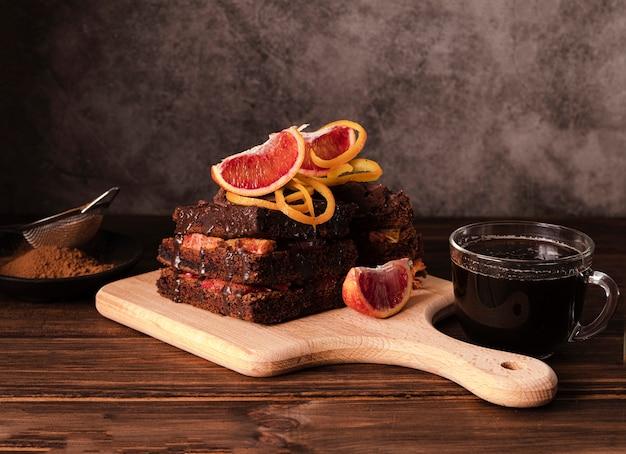 Alto angolo di torta al cioccolato sul tagliere con frutta Foto Gratuite