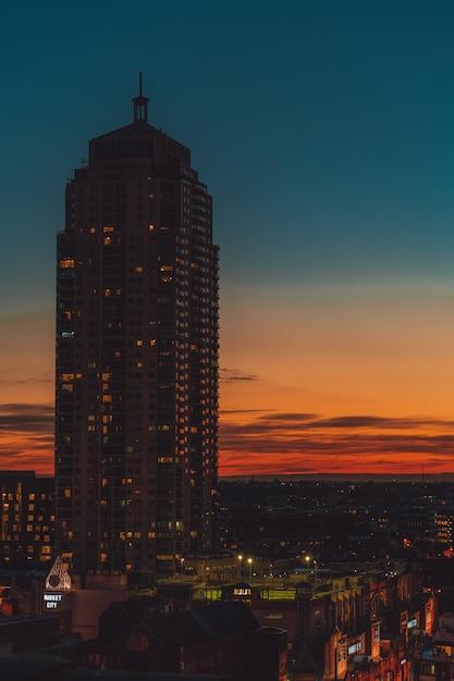 Alto edificio con un cielo arancione e blu Foto Gratuite