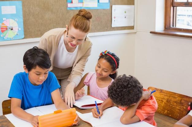 Alunni carini ottenere aiuto dall'insegnante in classe Foto Premium