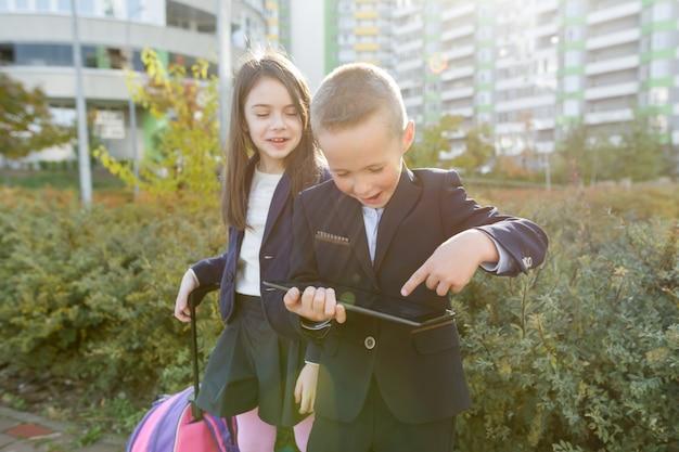 Alunni della ragazza e del ragazzo a scuola primaria con la compressa digitale Foto Premium