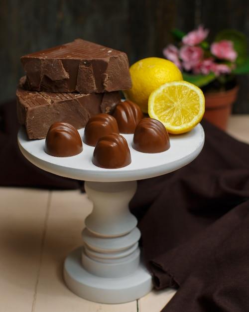 Alzata bianca piccola con cioccolatini al latte e limone in cima Foto Gratuite