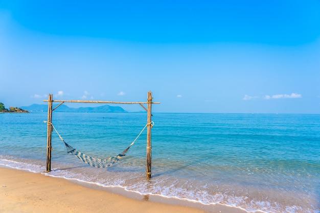 Amaca vuota altalena sulla bellissima spiaggia e mare Foto Gratuite