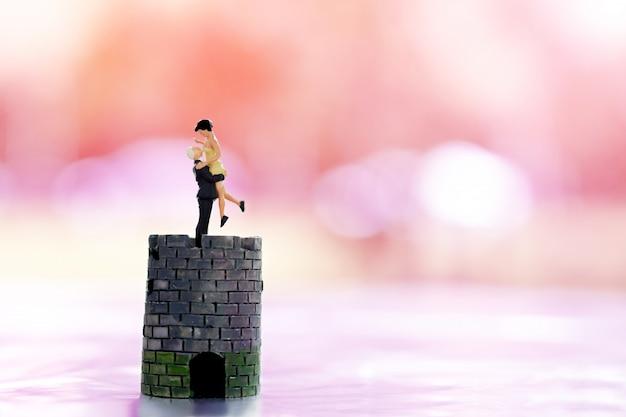 Amante miniatura delle coppie della gente che sta sul castello e sulla casa minuscola con fondo rosa. Foto Premium