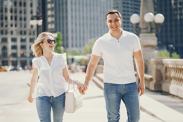 Amanti giovani ed eleganti coppia in magliette bianche e blue jeans camminando in una grande città Foto Gratuite