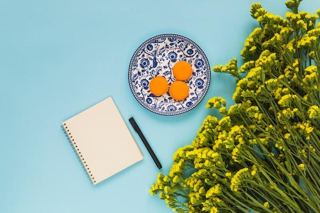 Amaretti su piatto di ceramica; blocco note a spirale; penna e mazzo di fiori gialli su sfondo blu Foto Gratuite