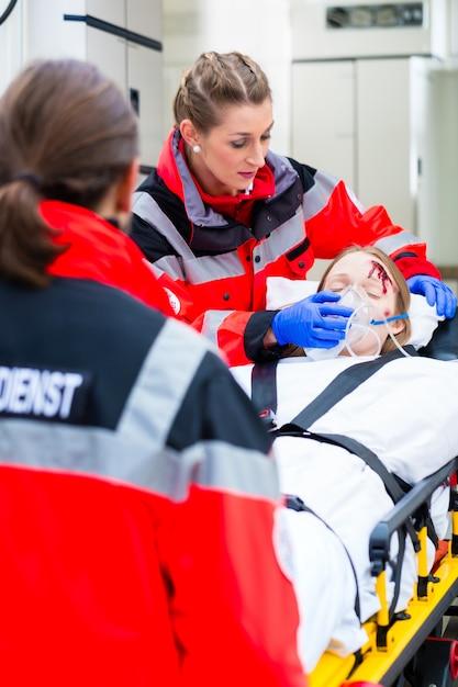 Ambulanza che aiuta donna ferita sulla barella Foto Premium