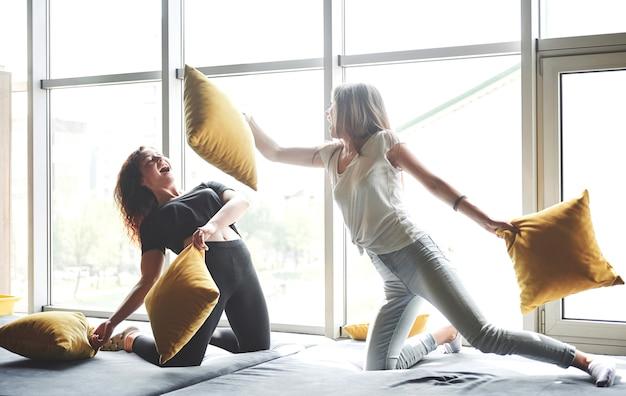 Amiche divertenti giocano a cuscini, vicino a grandi finestre. Foto Gratuite