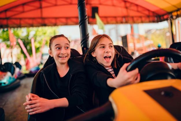 Amiche nel parco divertimenti guida auto paraurti Foto Premium