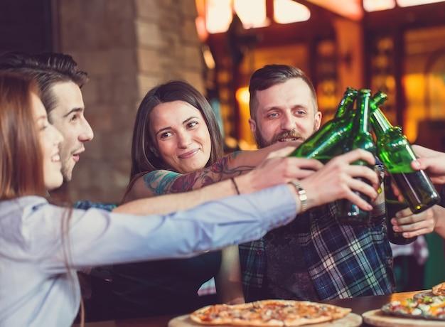 Amici a bere qualcosa e mangiare pizze in un bar Foto Premium