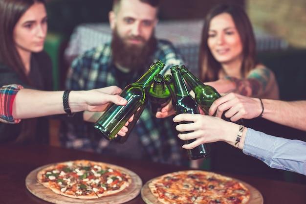 Amici a bere qualcosa in un bar, sono seduti a un tavolo di legno con birre e pizza. Foto Premium