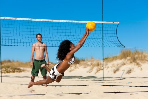 Amici a giocare a beach volley Foto Premium