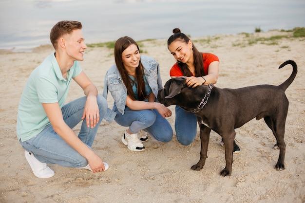 Amici a tutto campo che giocano con un bellissimo cane Foto Gratuite
