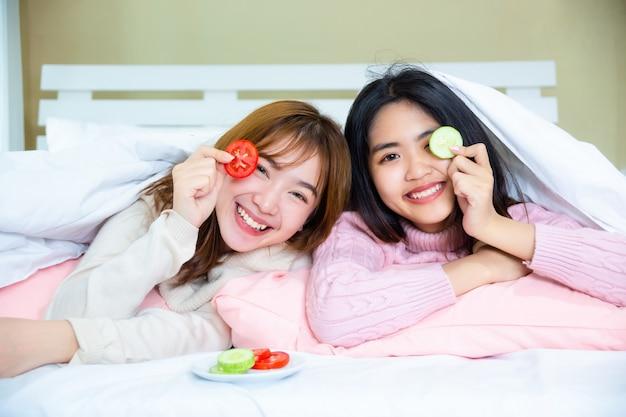 Amici adolescenti che si trovano sotto la coperta con cuscini sul letto Foto Gratuite