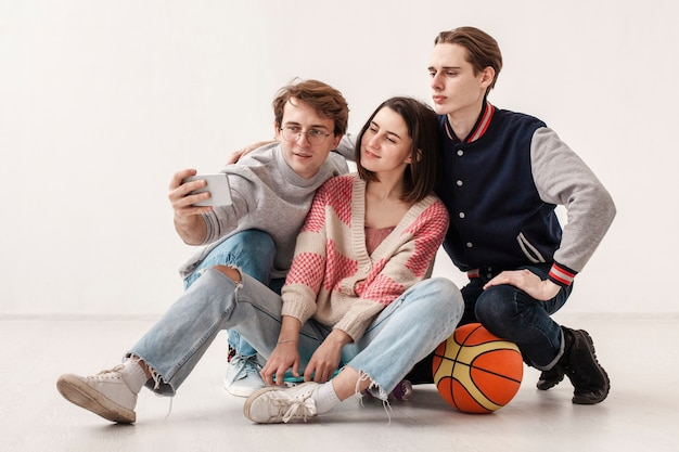 Amici adolescenti di angolo basso che prendono selfie Foto Gratuite