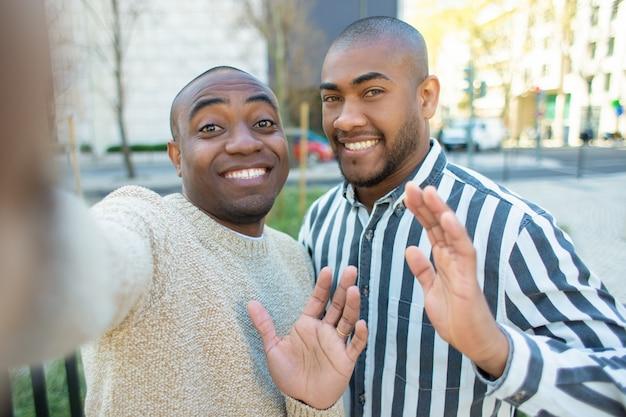 Amici afroamericani sorridenti che ondeggiano mentre prendendo selfie Foto Gratuite