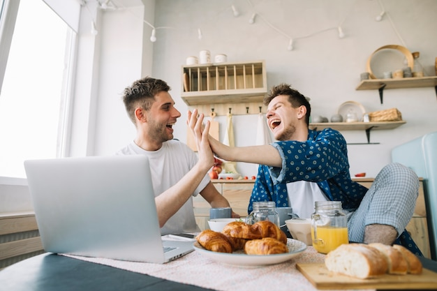 Amici allegri che applaudono le mani che si siedono davanti alla tavola con la prima colazione ed il computer portatile Foto Gratuite