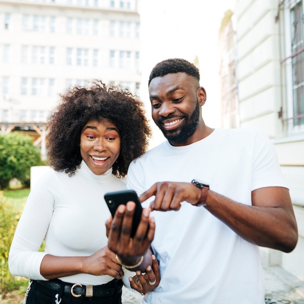 Amici allegri che guardano il cellulare Foto Gratuite