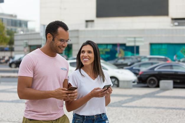 Amici allegri che passeggiano sulla strada con gli smartphone Foto Gratuite