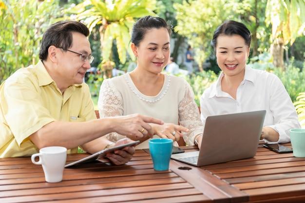 Amici asiatici anziani che utilizzano i computer portatili e le compresse nella casa di cura. Foto Premium
