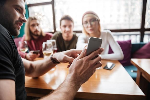 Amici attraenti che si siedono in caffè e guardando il telefono. Foto Gratuite