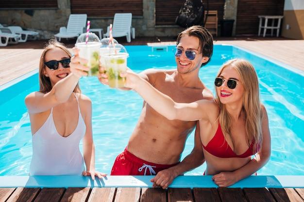 Amici brindando con cocktail in piscina Foto Gratuite
