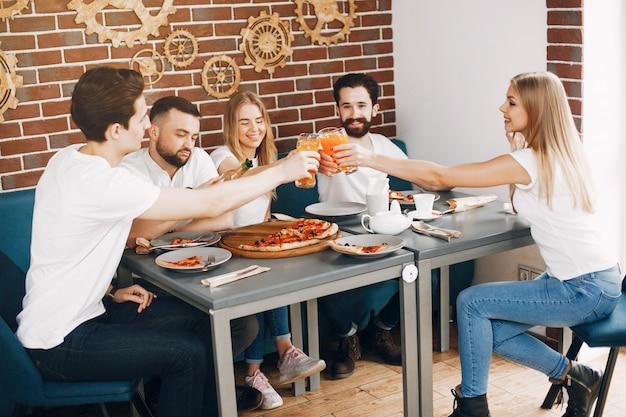 Amici carini in un caffè eatting una pizza Foto Gratuite
