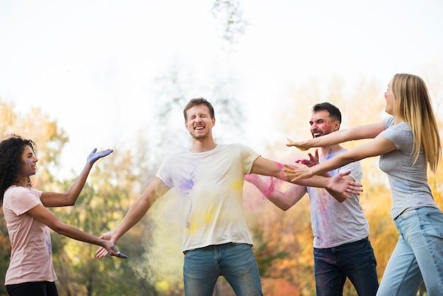 Amici che celebrano holi in natura Foto Gratuite