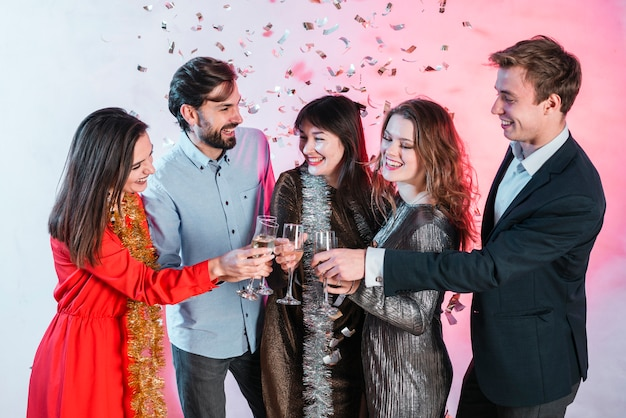 Amici che celebrano il natale e bicchieri di champagne tintinnanti Foto Gratuite