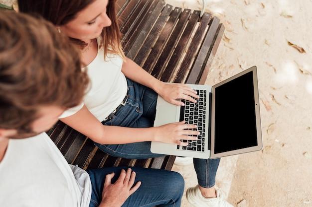 Amici che controllano computer portatile su un banco Foto Gratuite