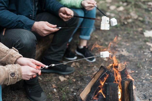 Amici che cucinano marshmallow al falò Foto Gratuite