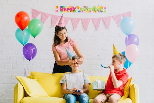 Amici che danno un regalo a sorpresa al ragazzo Foto Gratuite