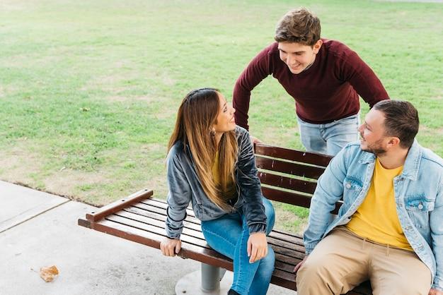 Amici che godono della giornata nel parco che si siede sulla panchina Foto Gratuite