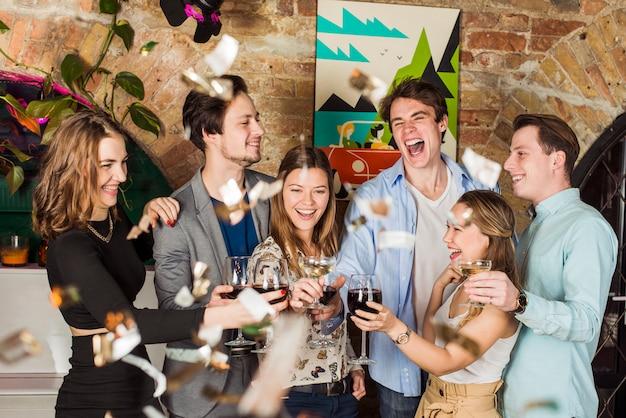 Amici che godono la festa con la tostatura del bicchiere di vino Foto Gratuite