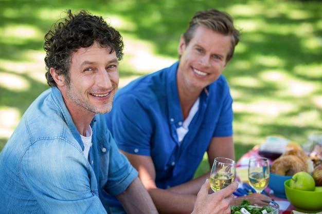 Amici che hanno un picnic con vino Foto Premium