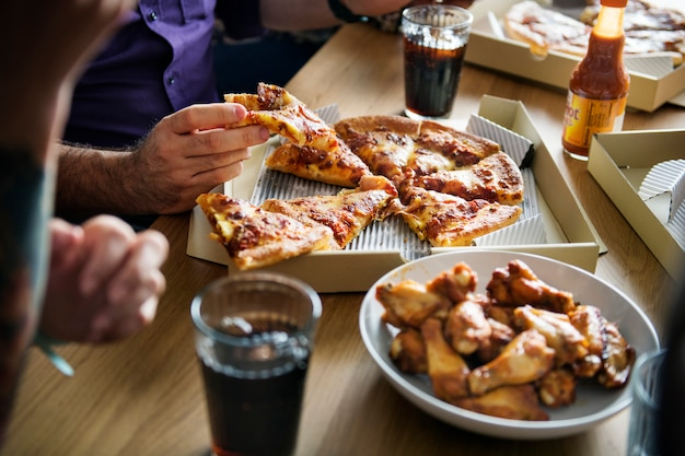 Amici che mangiano pizza insieme a casa Foto Premium
