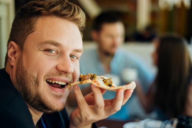 Amici che mangiano pizza seduti in un caffè Foto Gratuite