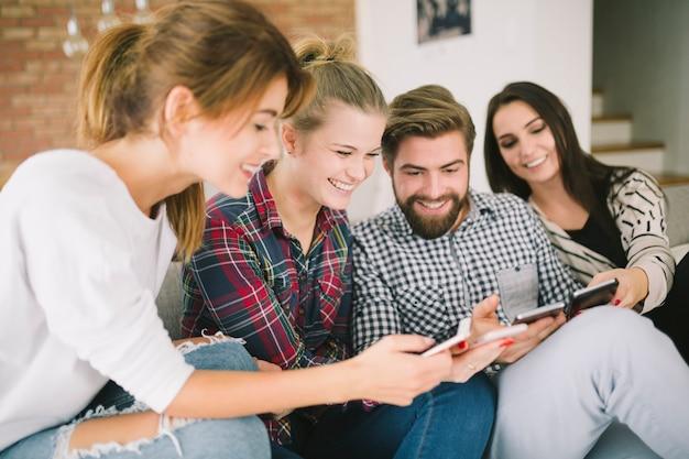 Amici che ridono utilizzando dispositivi seduti sul divano Foto Gratuite