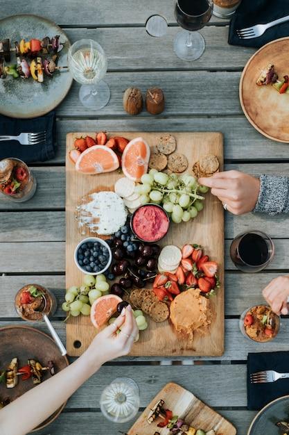 Amici che si godono un piatto di frutta Foto Gratuite