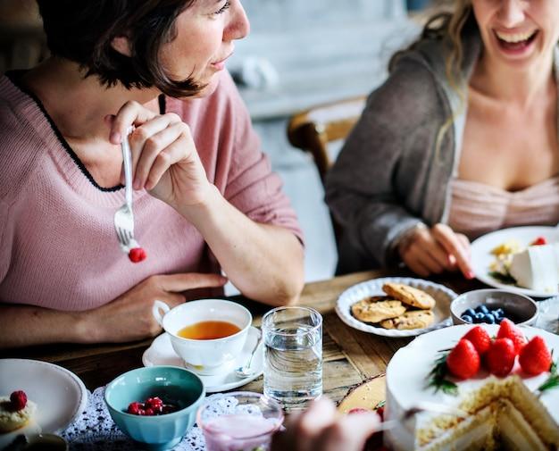 Amici che si riuniscono insieme su tea party eating cakes enjoyment happiness Foto Premium