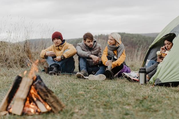Amici che si scaldano sul fuoco Foto Gratuite