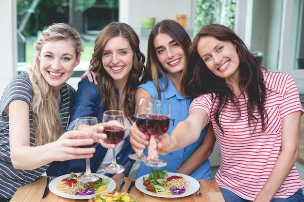 Amici che tengono vetro di vino rosso mentre consumando pasto Foto Premium