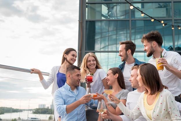 Amici che tostano a una festa in terrazza Foto Gratuite