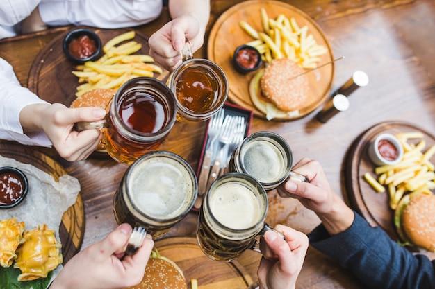 Amici che tostano con la birra nel ristorante Foto Gratuite
