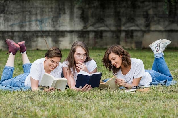 Amici degli studenti di college che leggono sdraiato sul prato Foto Gratuite