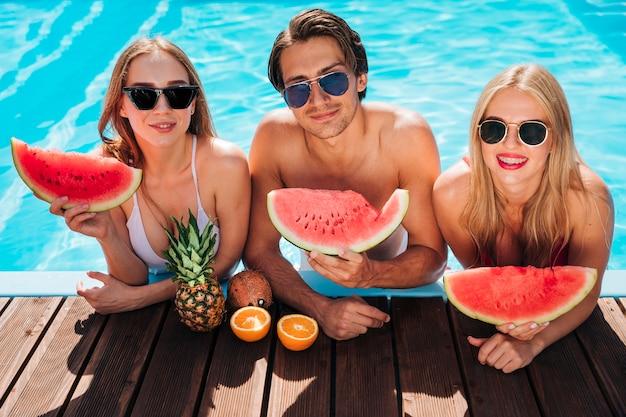 Amici del colpo medio in piscina che guarda l'obbiettivo Foto Gratuite