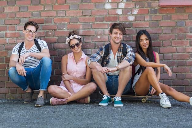Amici dell'anca che si siedono sul pavimento contro il muro sulla strada Foto Premium