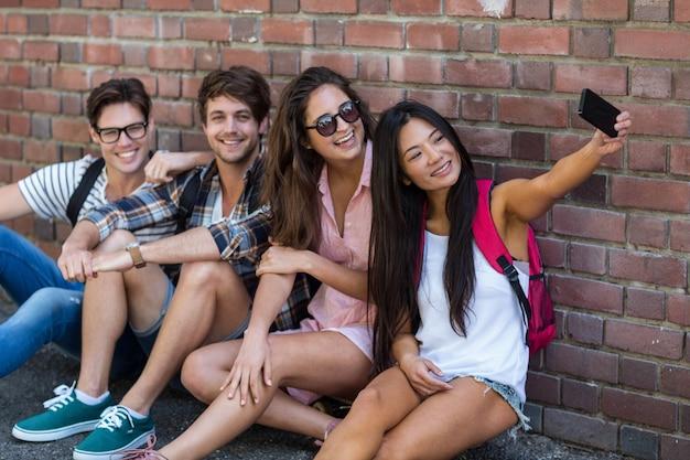 Amici dell'anca che si siedono sul pavimento e che prendono selfie contro il muro di mattoni Foto Premium