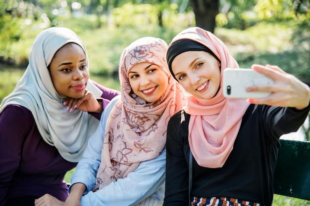 Amici delle donne islamiche prendendo selfie insieme Foto Premium